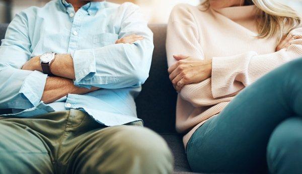 Eine Frau zieht dem Mann Geld aus der Tasche: Paare müssen über ihre Finanzen in der Ehe reden.