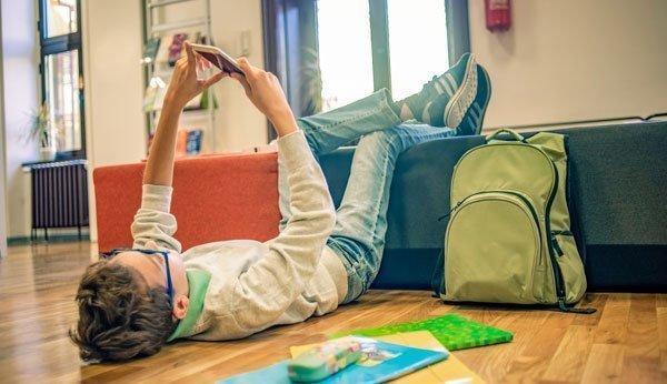 Das Handy als ständiger Begleiter: Ein junger Mann schaut nach der Schule direkt aufs Smartphone.